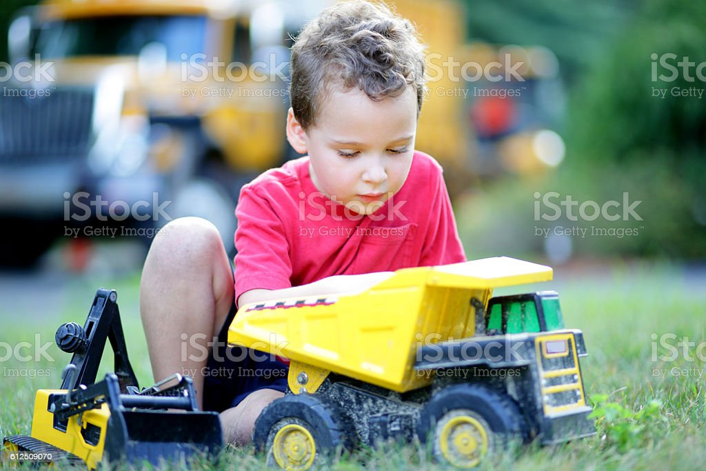 Boy playing with toy trucks on his front lawn stock photo