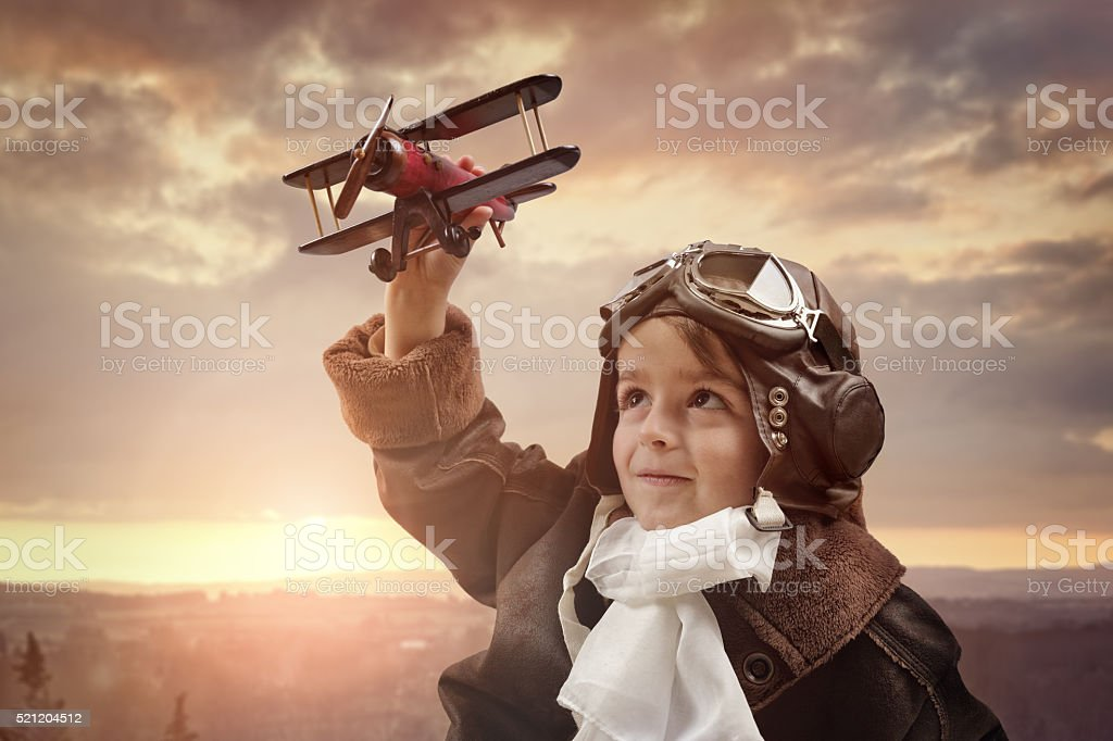 Boy playing with wooden toy airplane stock photo