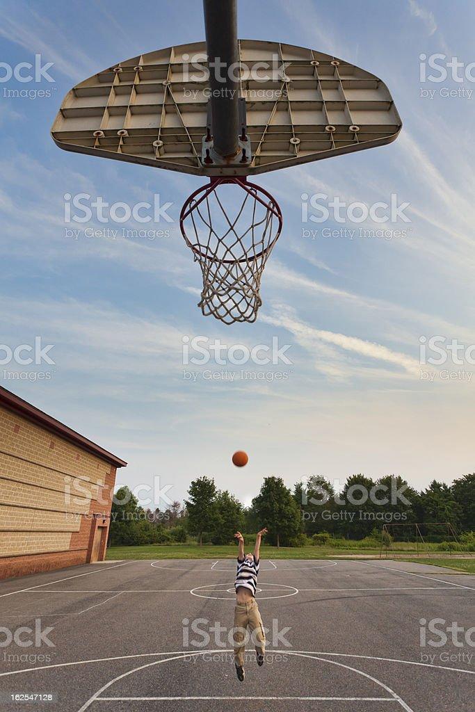 Boy plays playground basketball stock photo