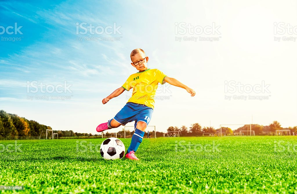 Boy plays soccer on field and kicks football stock photo