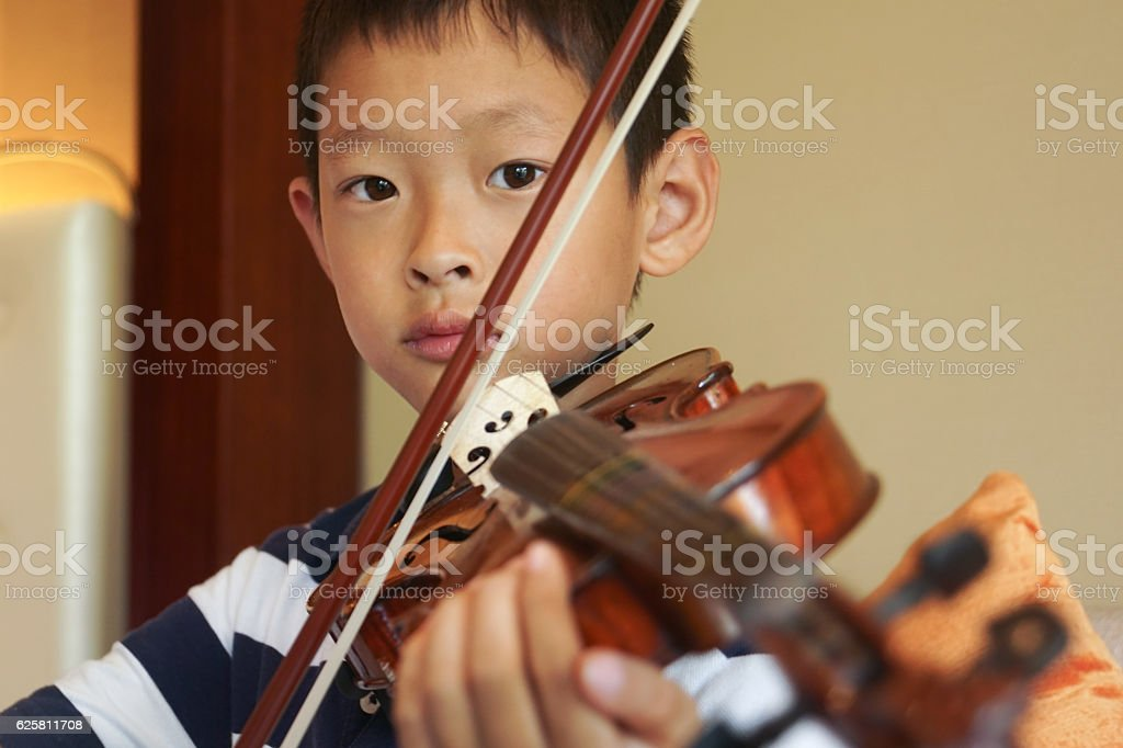 boy plays voilin stock photo