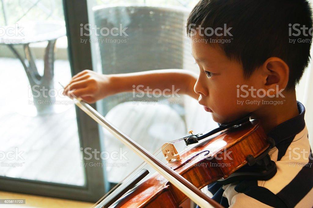 boy plays voilin stock photo