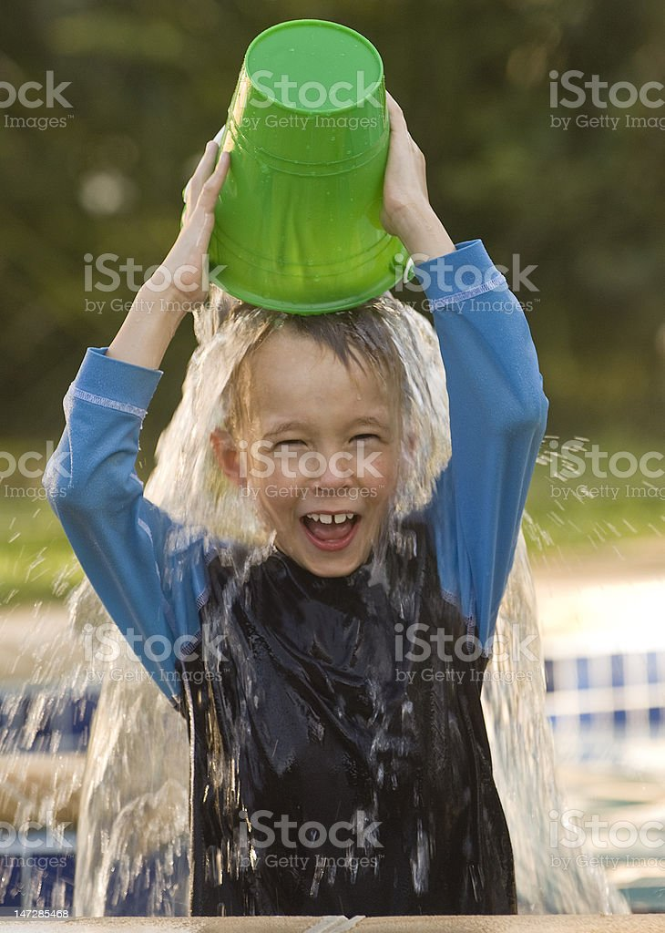 Boy plays with bucket of water in swimming pool royalty-free stock photo