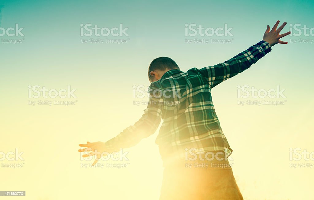 Boy plays with the light as the sun sets stock photo