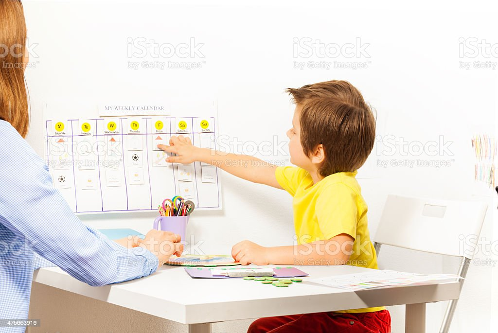Boy points at activities on calendar learning days stock photo