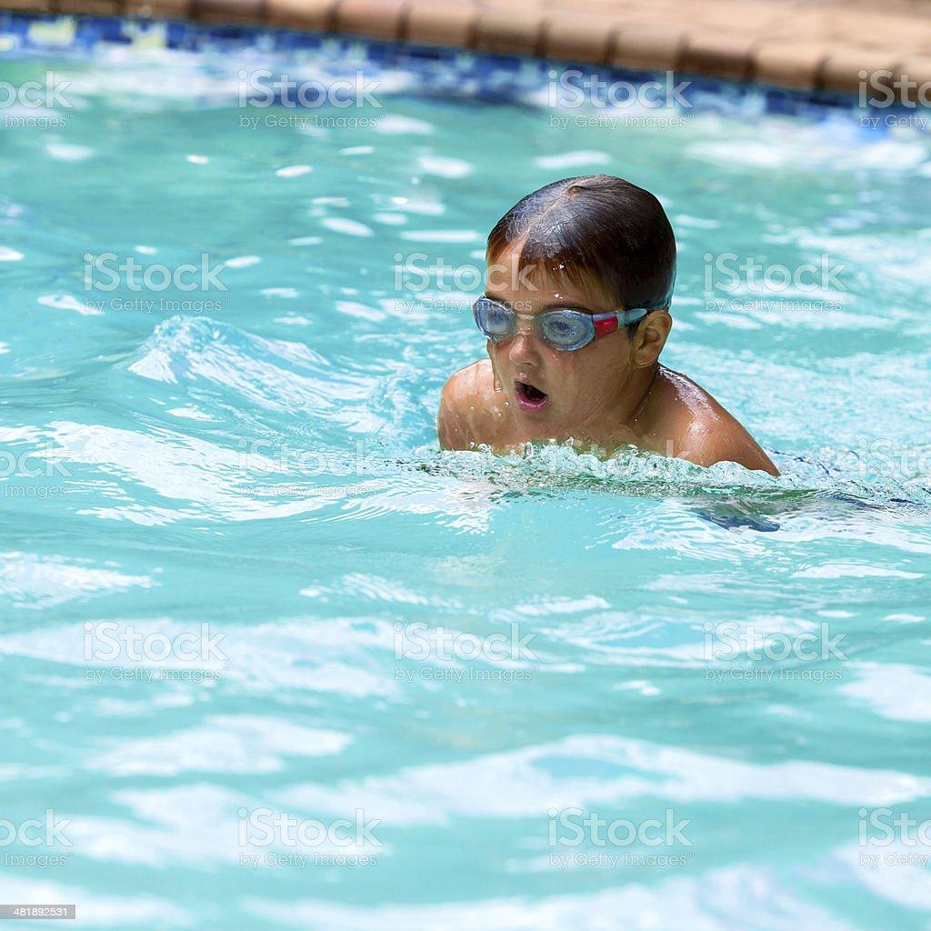 Petit garçon pratiquant le brasse dans la piscine. photo libre de droits