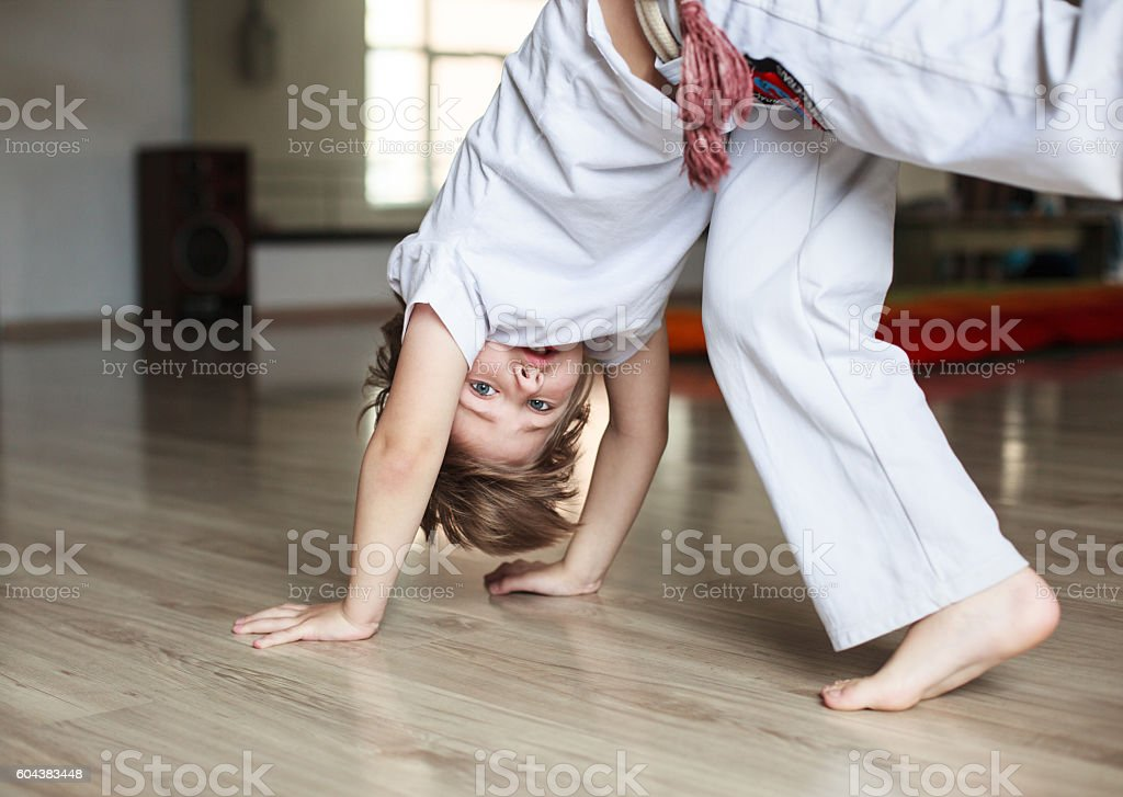 Boy  practicing capoeira  in gym stock photo