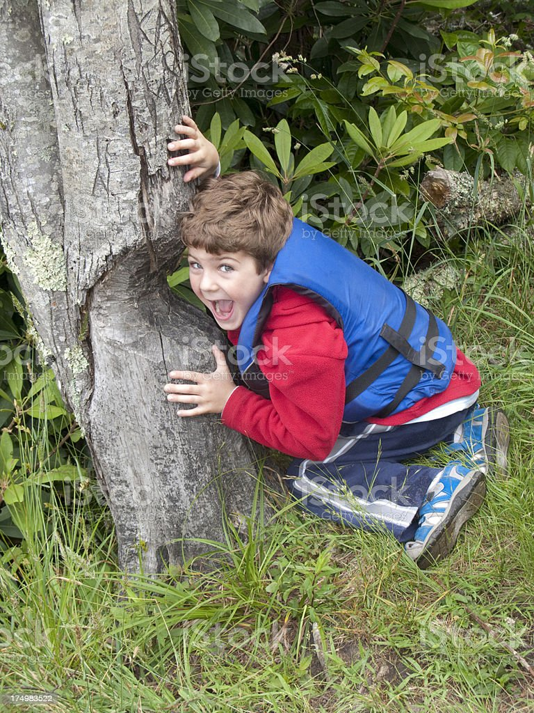 Boy Pretending To Be a Beaver Eating Tree stock photo