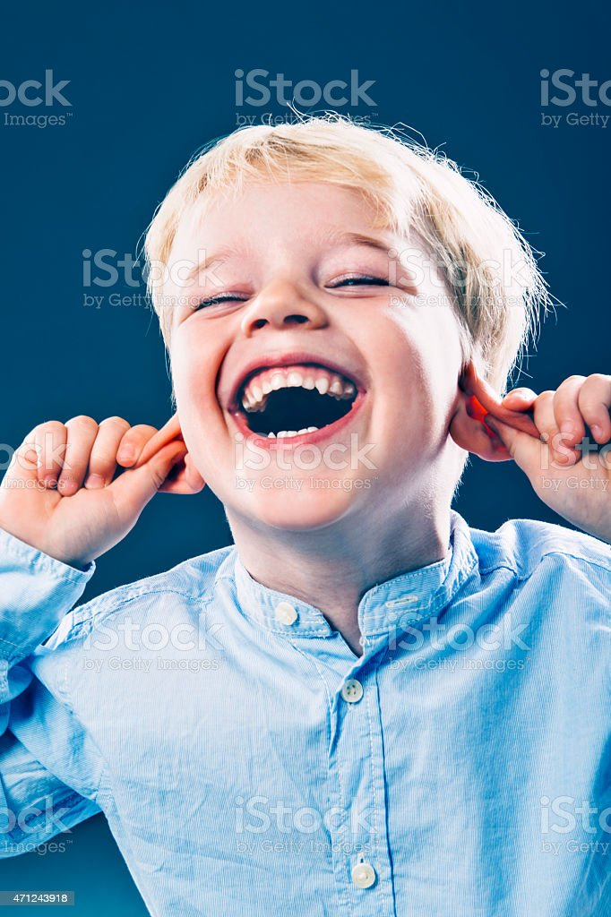 Boy pulls his ears while laughing and having fun stock photo