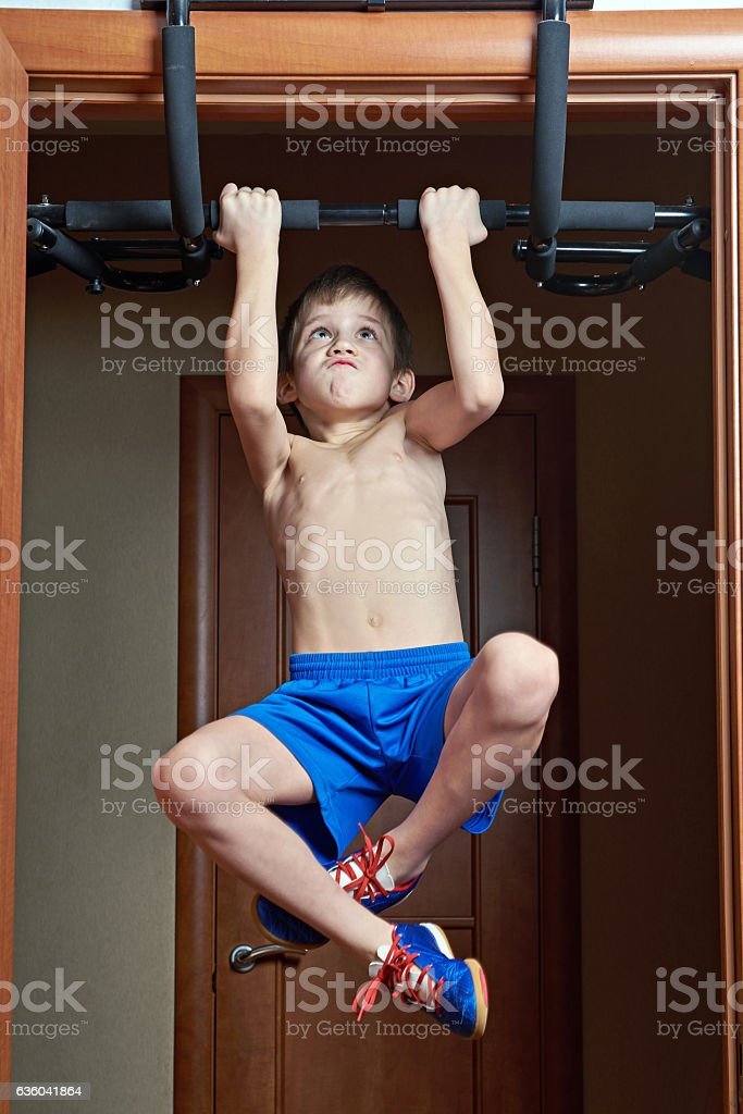Boy pulls on bar at home stock photo