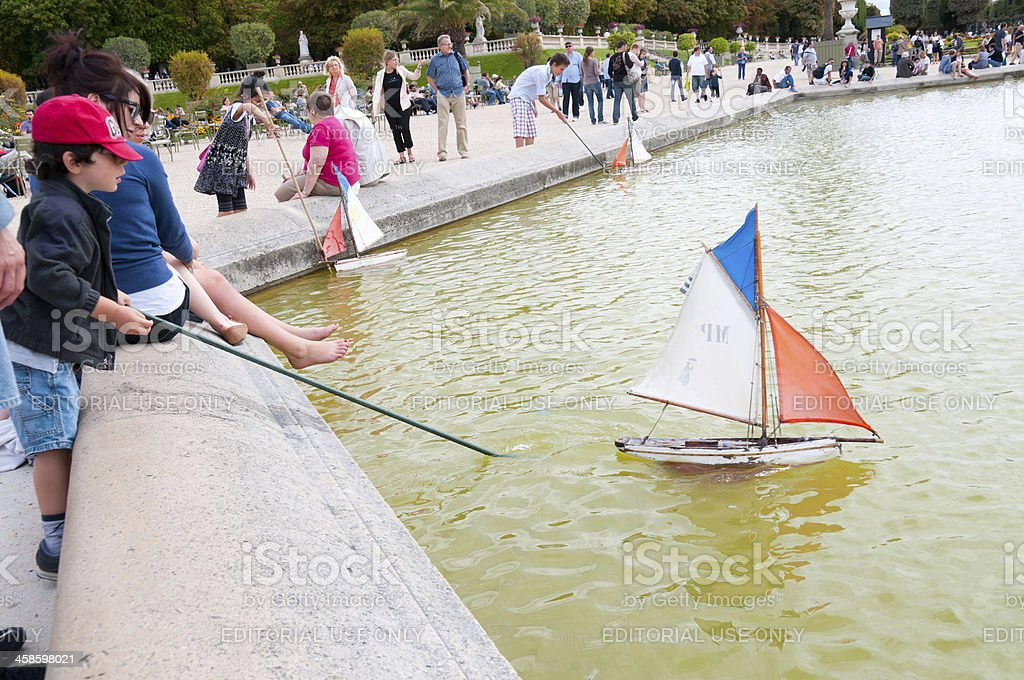 Boy pushing a toy boat at Luxembourg Gardens, Paris stock photo