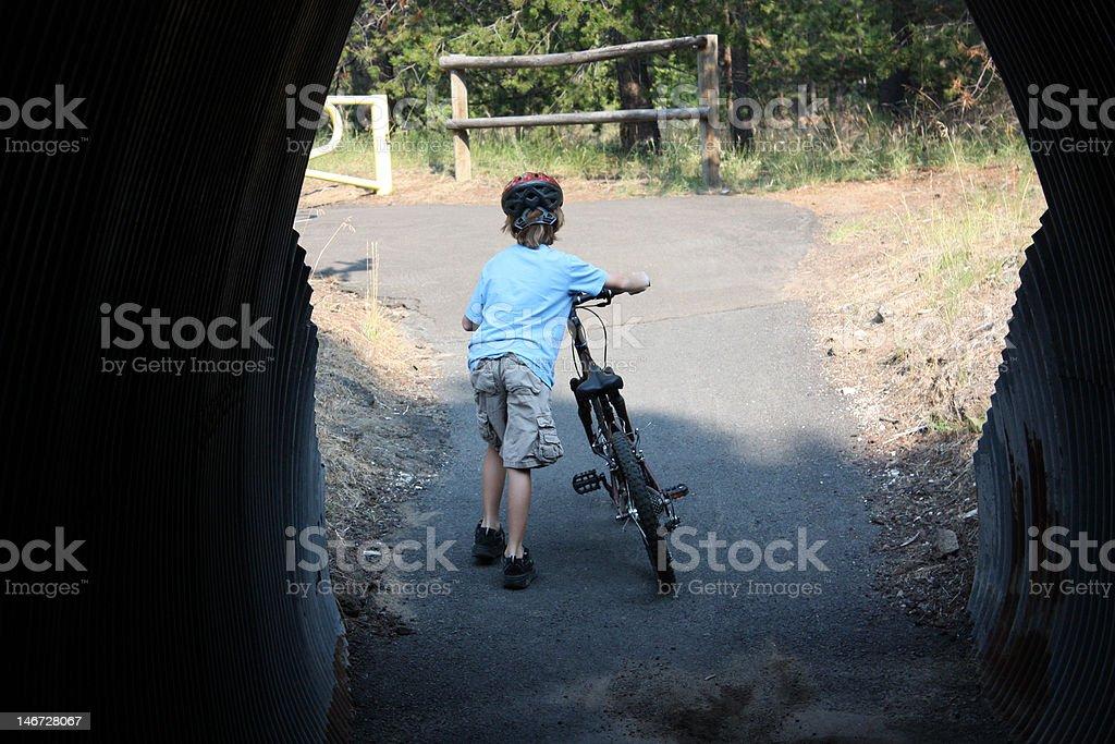 Garçon pousse vélo dans le tunnel photo libre de droits