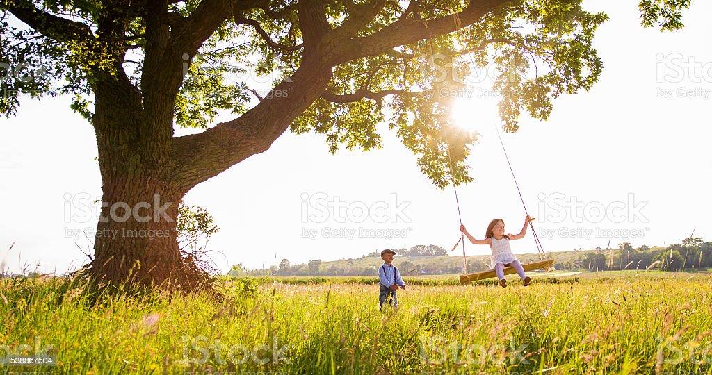Boy pushing female friend on swing on grassy field stock photo