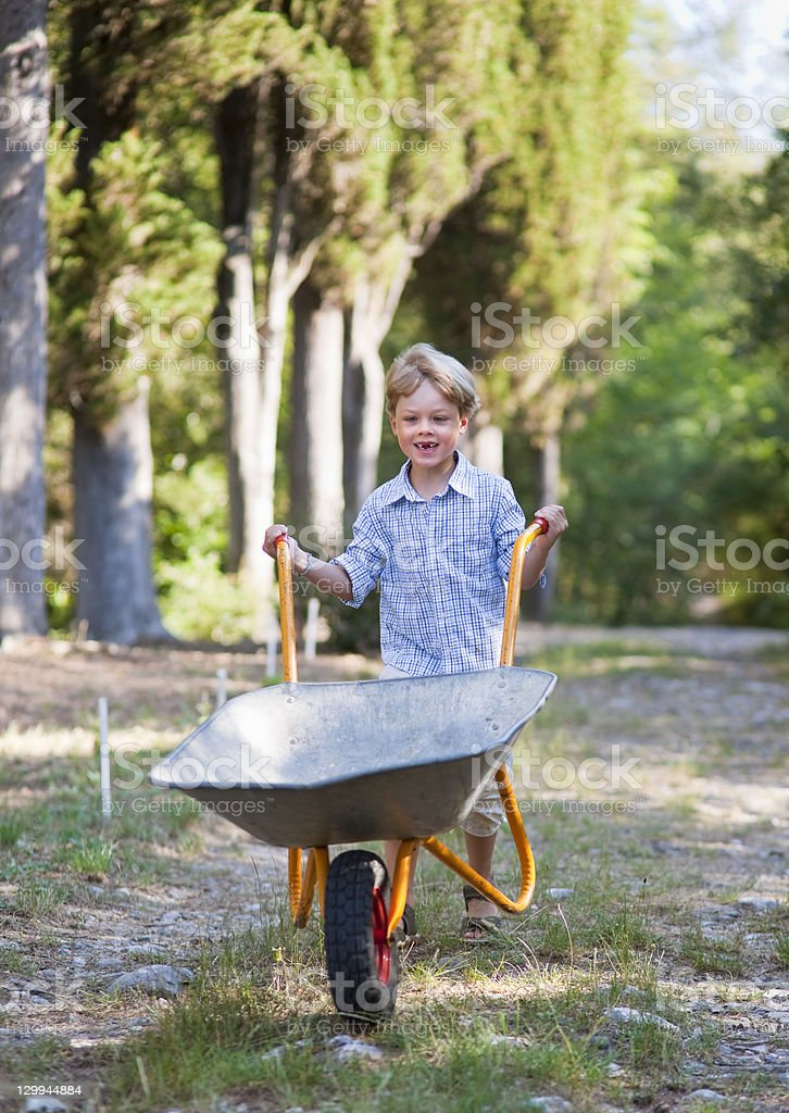 Boy pushing wheelbarrow outdoors stock photo