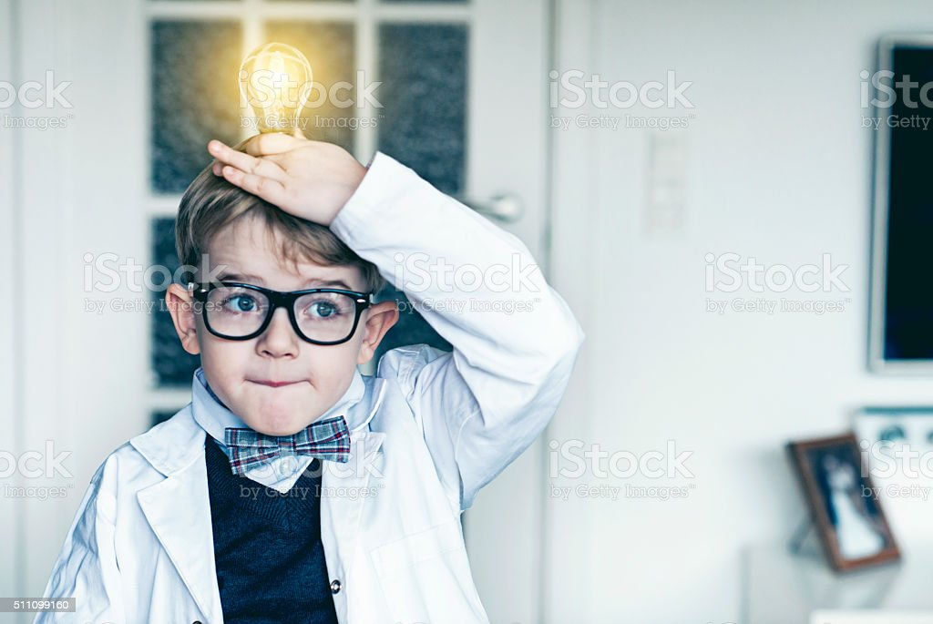 Boy puts light bulb on top head and gets idea stock photo