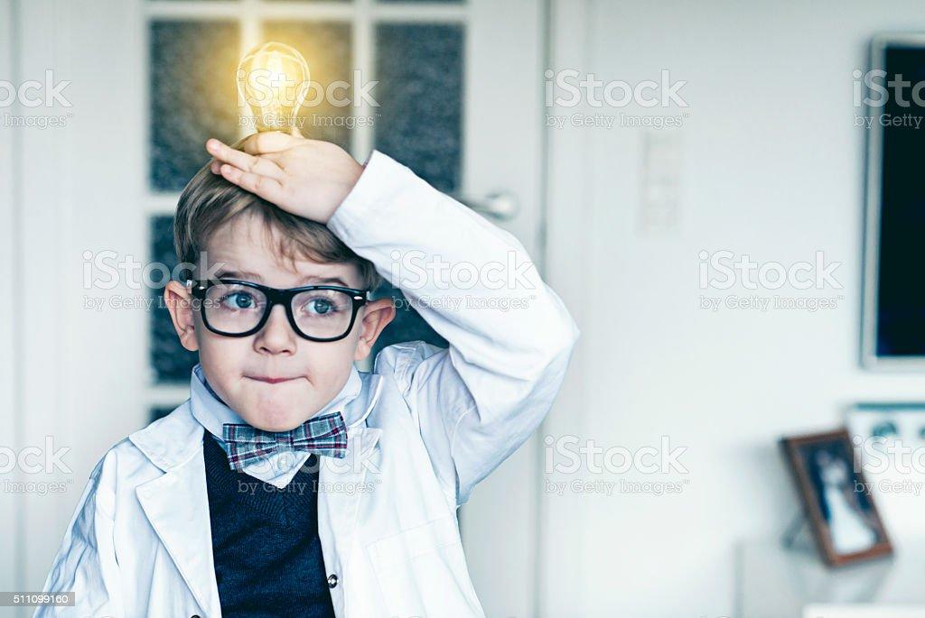 Boy puts light bulb on top head and gets idea stock photo