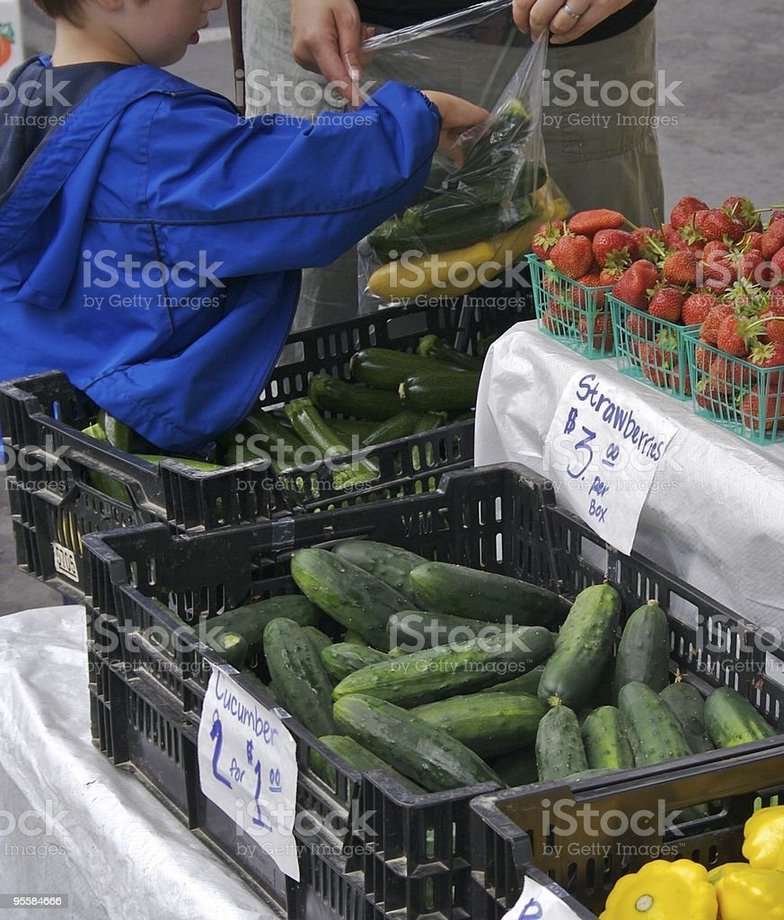 Boy puts vegetables in bag at Farmers Market stock photo