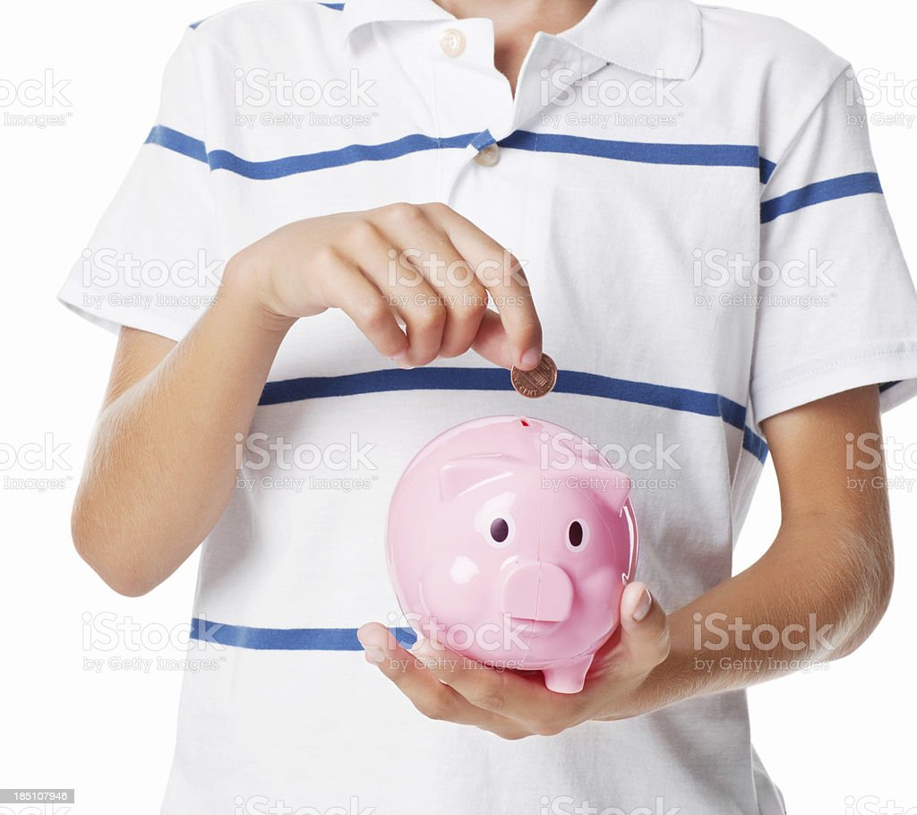 Boy Putting Coin In Piggy Bank - Isolated stock photo
