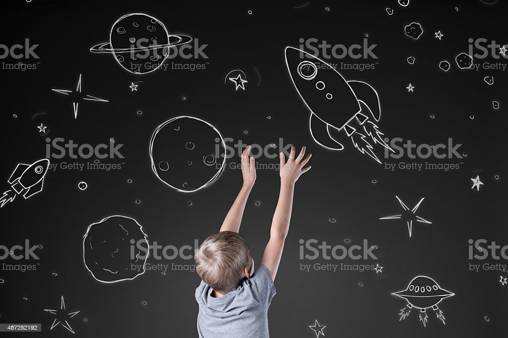 Boy reaching for rocket stock photo