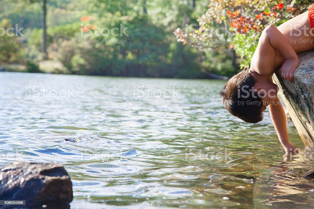 Boy reaching into water in lake stock photo