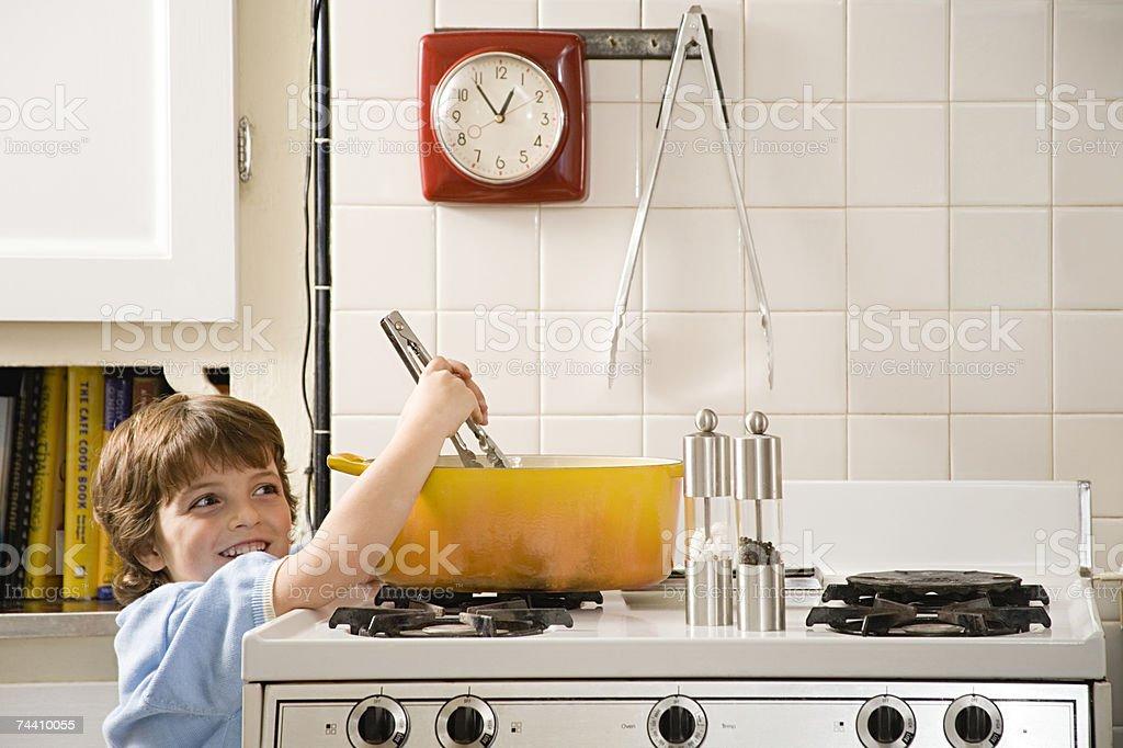 Boy reaching up to saucepan royalty-free stock photo