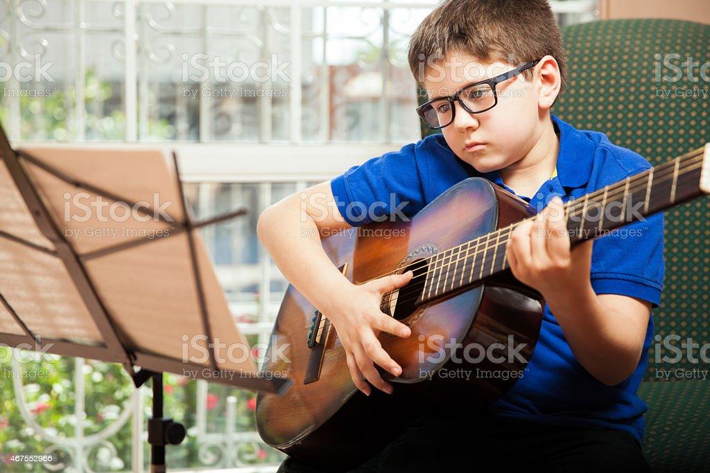 Boy reading a guitar sheet music stock photo