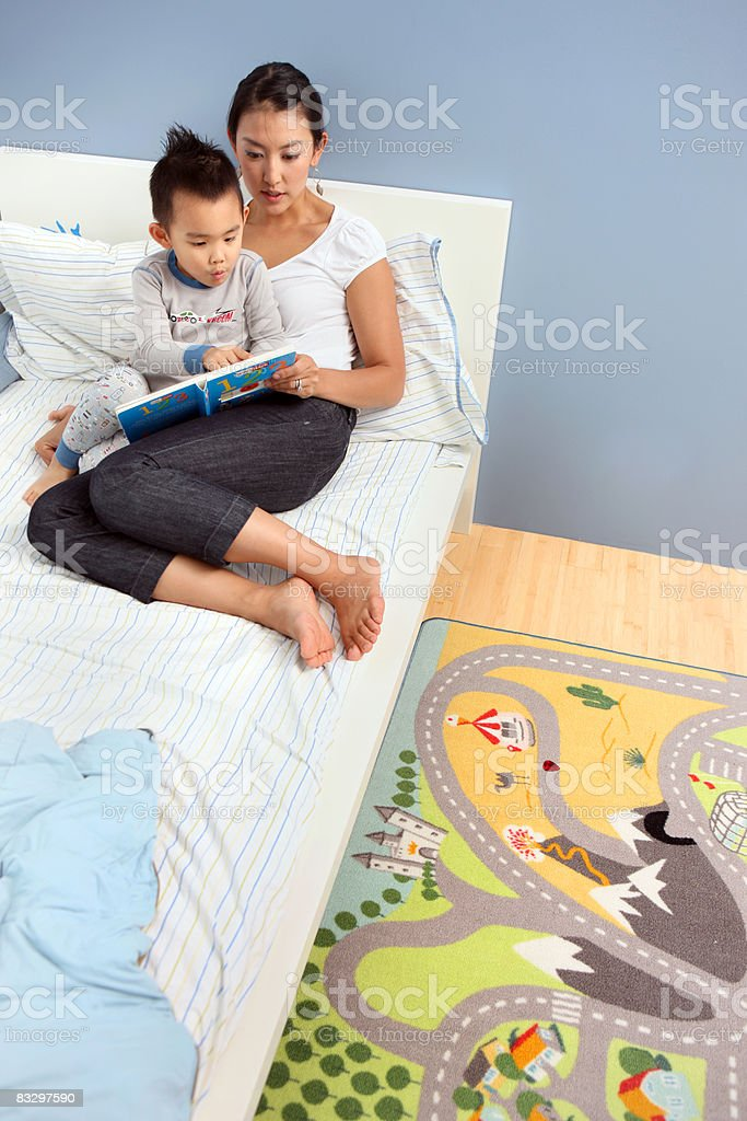 Boy reading book with mom. stock photo