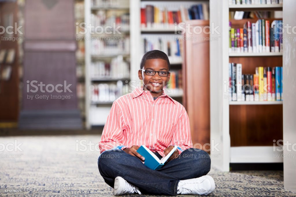 Boy reading in library stock photo