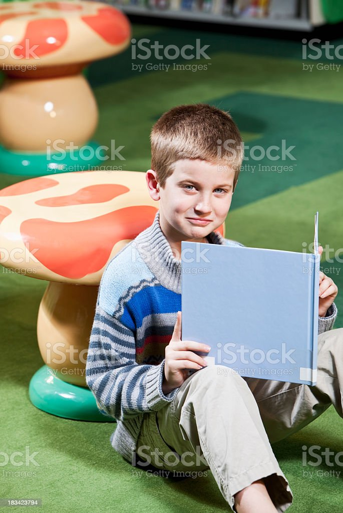 Boy reading in the library stock photo