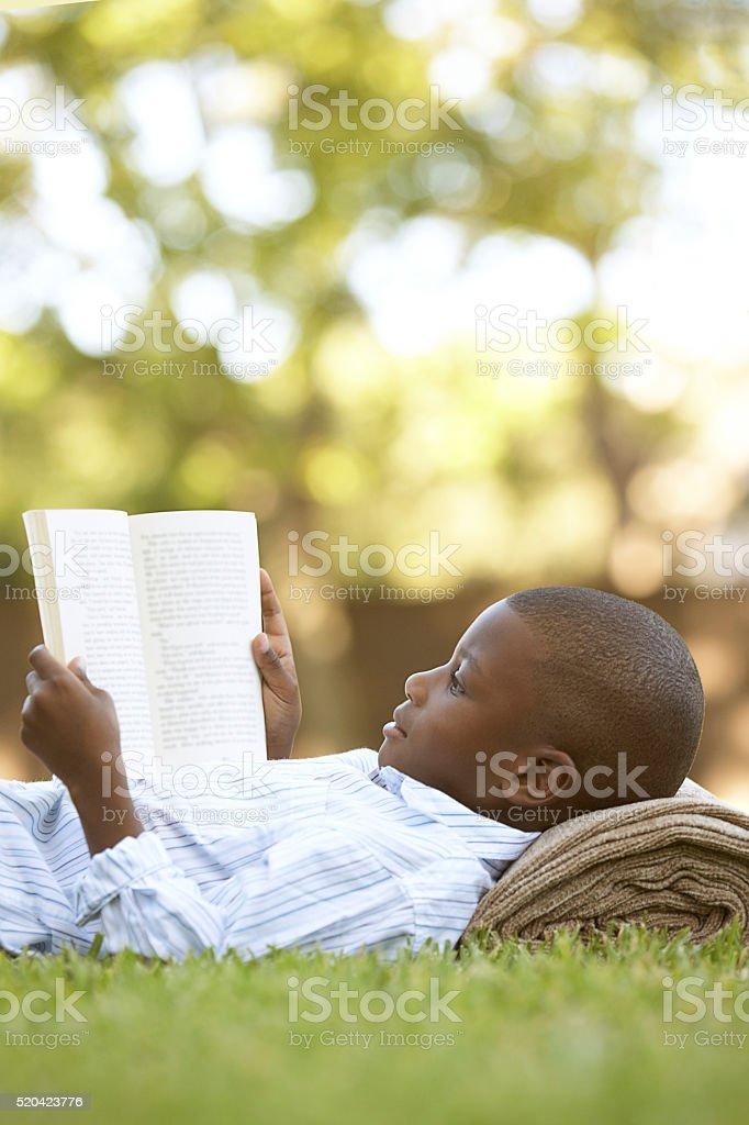 Boy reading outdoors stock photo