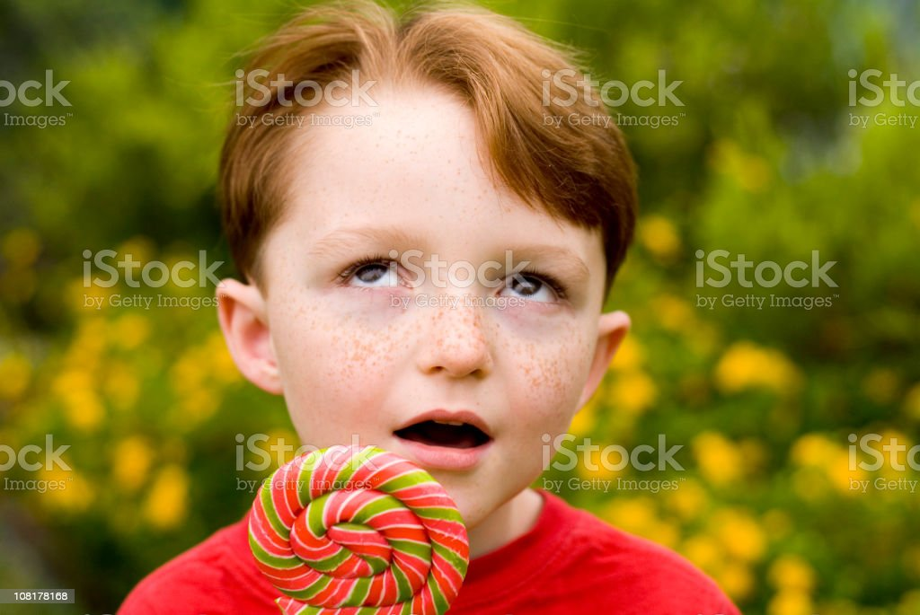 Boy Redhead Freckle Face, Child with Lollipop Candy Rolling Eyes royalty-free stock photo