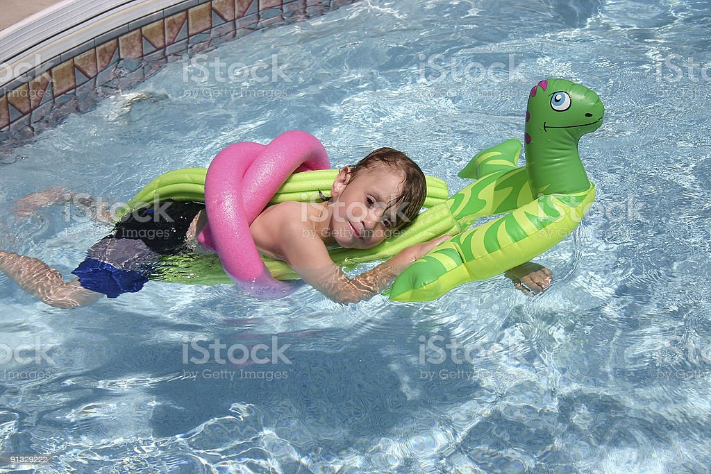 Boy Relaxing in pool stock photo