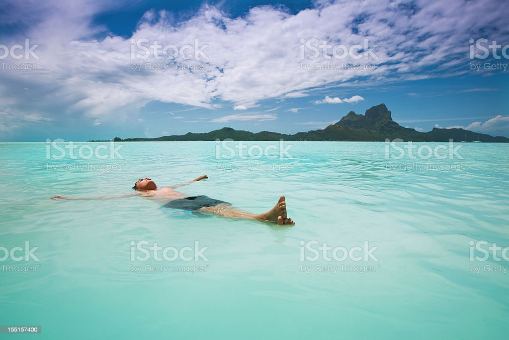 Boy relaxing in south pacific Bora-Bora island lagoon royalty-free stock photo