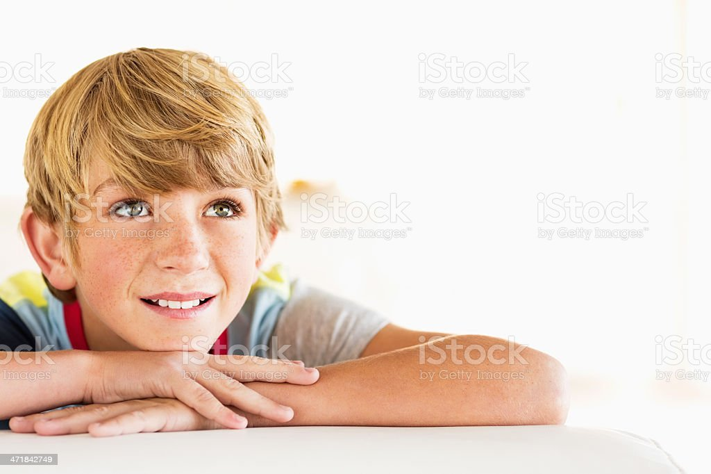 Boy Resting On Armrest While Looking Away At Home royalty-free stock photo