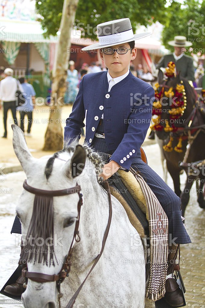 boy ridding a horse during the April Fair in Seville stock photo