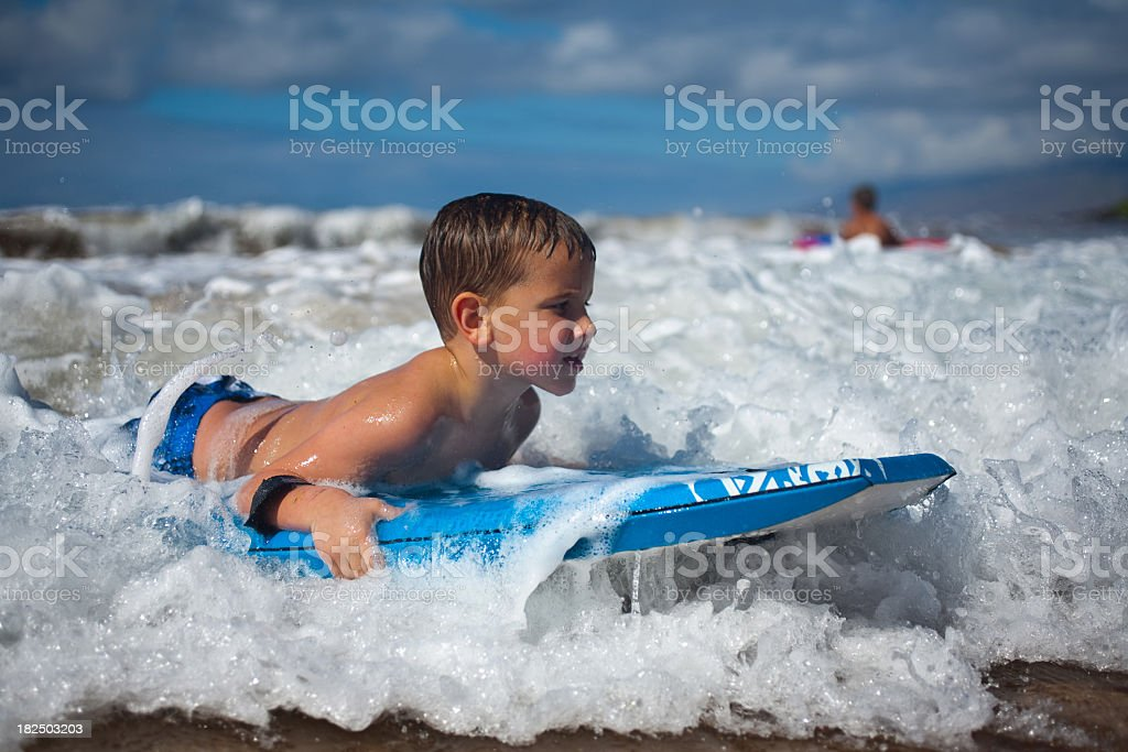 A boy rides on his boogie boarder stock photo