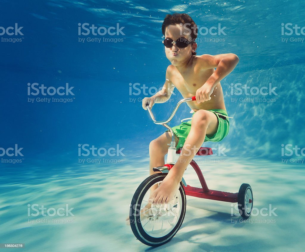 boy riding a tricycle underwater stock photo