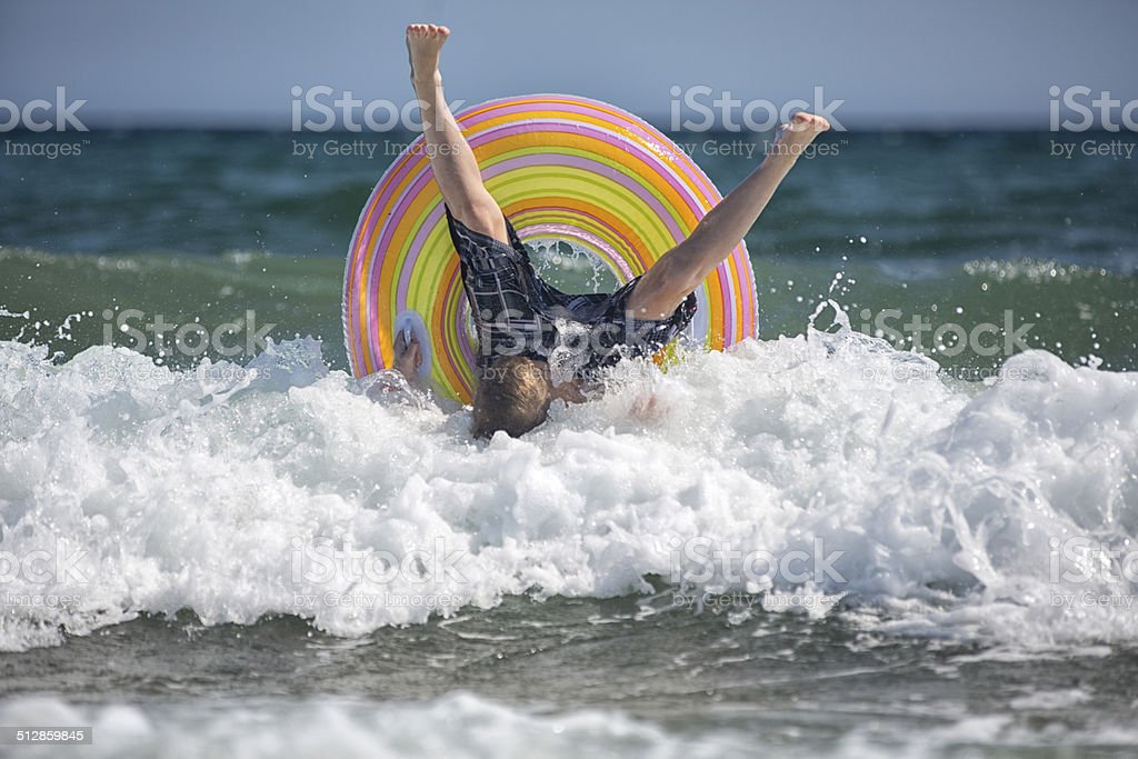 Boy riding a wave on an inter tube stock photo