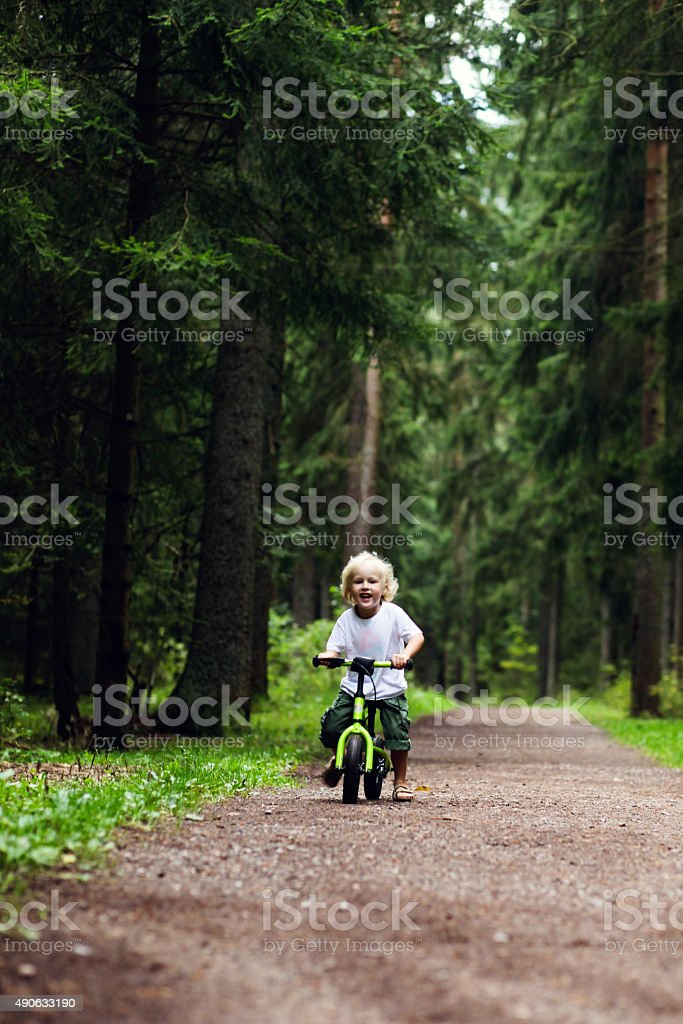 Boy riding balance bike in the forest stock photo