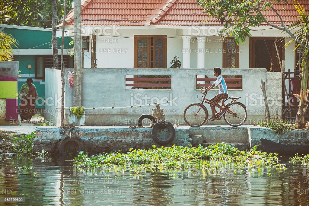 Boy riding bicycle along the Kerala Backwaters in India stock photo