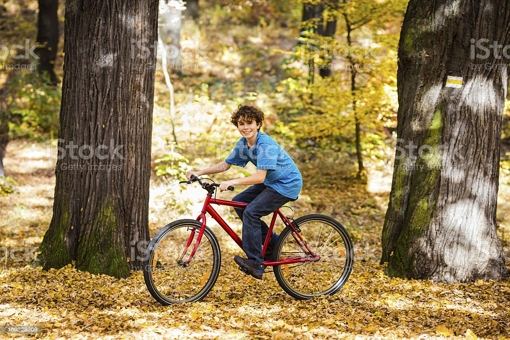 Boy riding bike in city park royalty-free stock photo