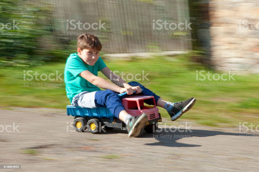 Boy Riding Downhill on Top of Toy Lorry stock photo