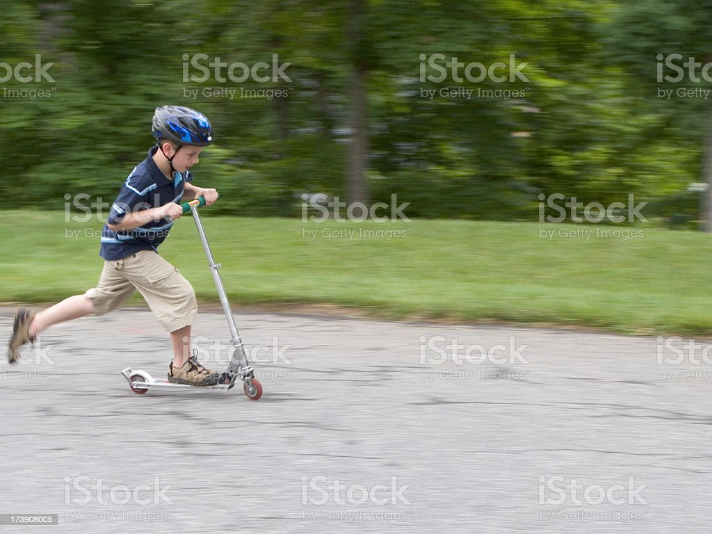 Boy Riding Fast On Scooter With Helmet. stock photo