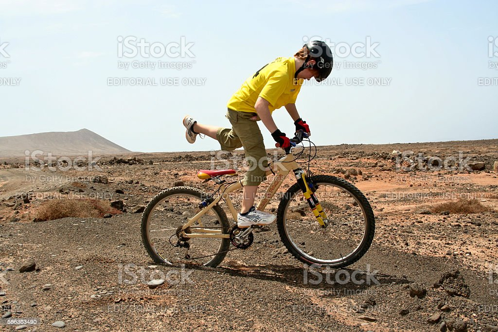 boy riding his mountainbike offroads and doing tricks stock photo