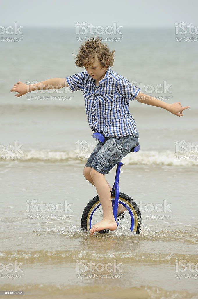 Boy Riding Unicycle in Sea royalty-free stock photo