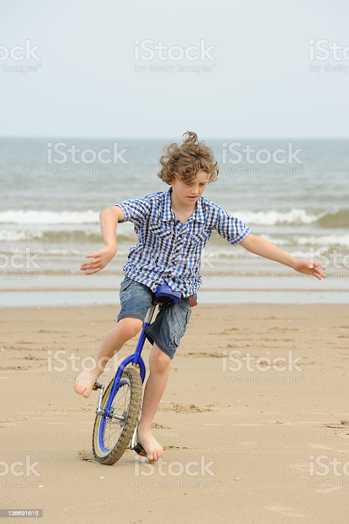 Boy Riding Unicycle on Beach royalty-free stock photo