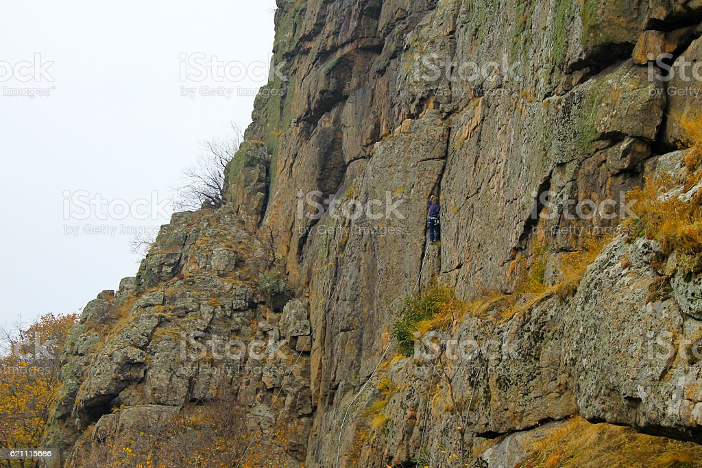 Boy rock climber climbs on a rock stock photo