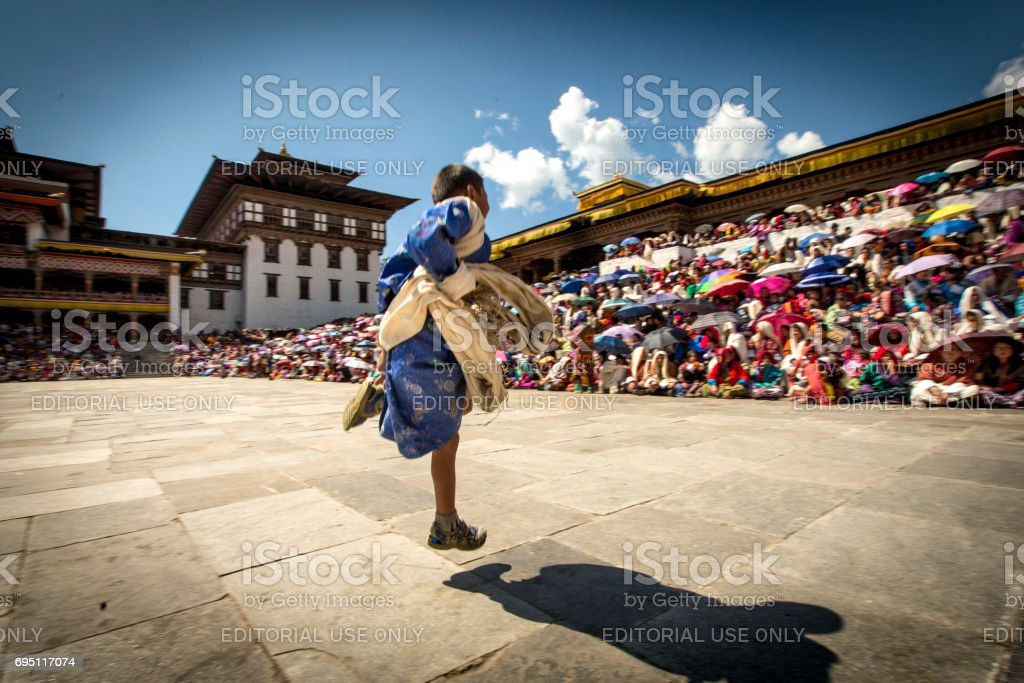 boy running across festival ground in Bhutan stock photo