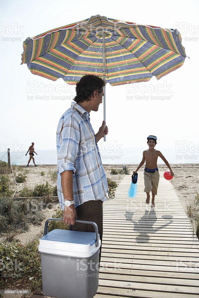 Boy (8-10) running along beach boardwalk towards father royalty-free stock photo