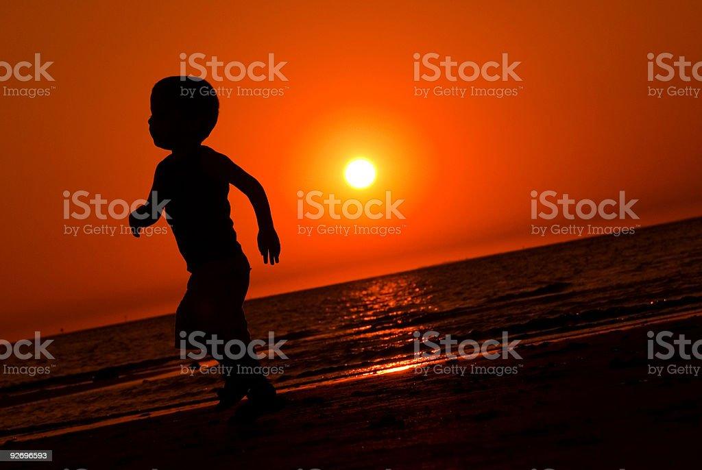 Boy running at sunset royalty-free stock photo